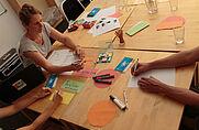 Gruppenberatung mit Trainerin und Arbeitsmaterialien am Tisch