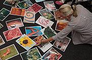 Workshopteilnehmer stehen um am Boden liegende Bilder