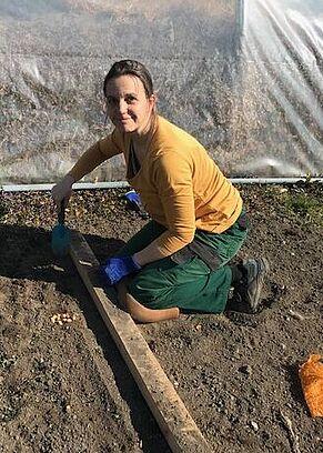 Eine Mitarbeiterin pflanzt Samen in die Erde